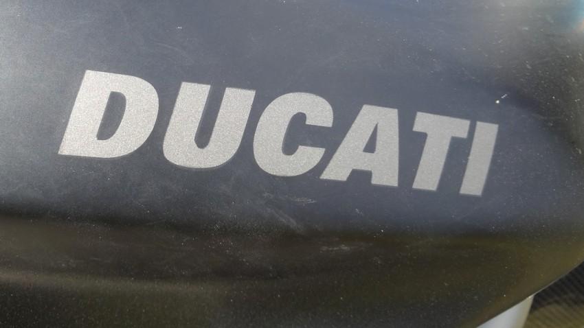 logo Ducati gris sur fond noir mat