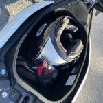 un casque et des gants sous la selle du NMax